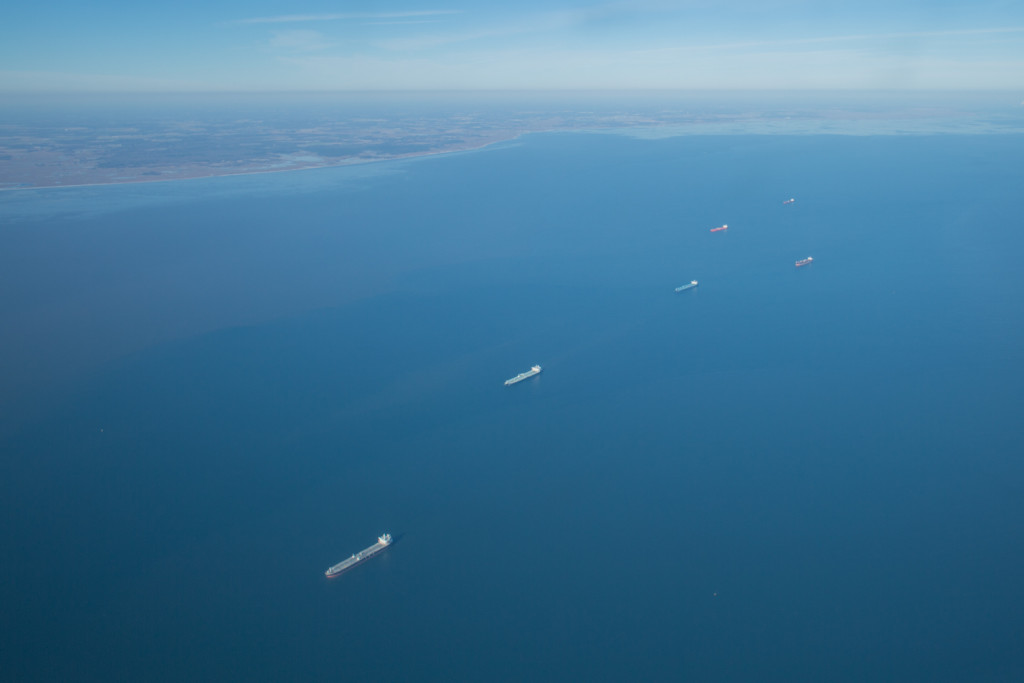 A line of colorful barges cruising out a blue Delaware Bay