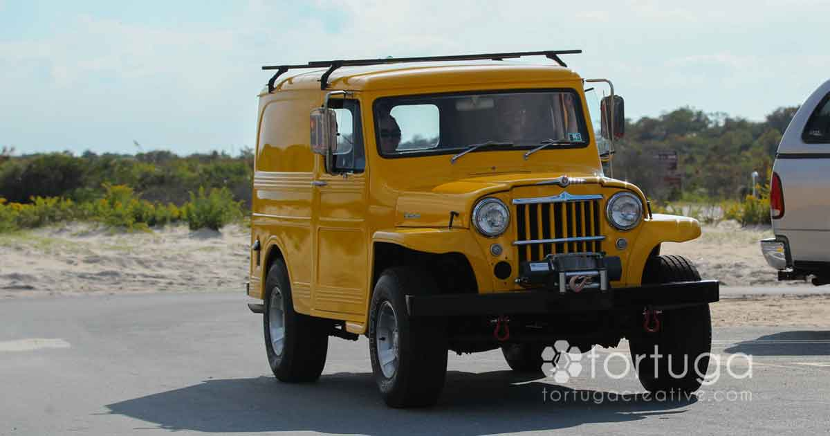 yellow jeep on beach dune